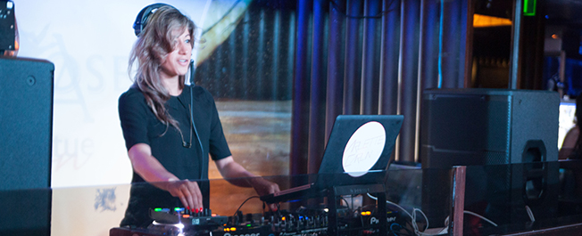 Female DJ performing live at musical event in NYC